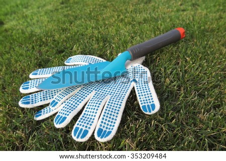 Garden scoop and working textile gloves on the mown lawn in the summer garden