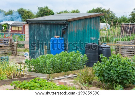 Garden shed with compost and water bins - stock photo
