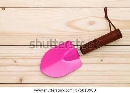 garden shovel on wood background - stock photo