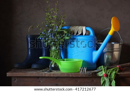 Garden still life with a spring bouquet watering can and rubber boots. Work in the garden, garden tools.