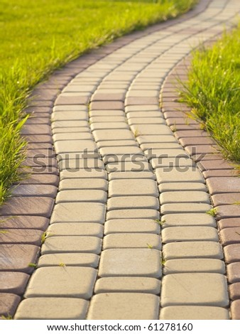 Garden stone path with grass growing up between and around stones, Brick Sidewalk - stock photo