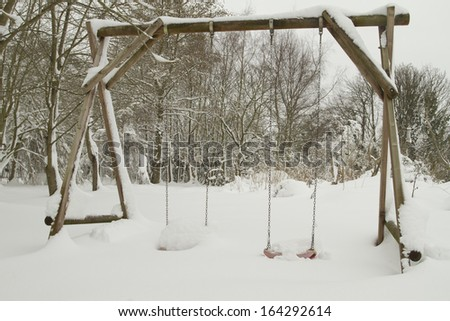 Garden swings covered in snow - stock photo