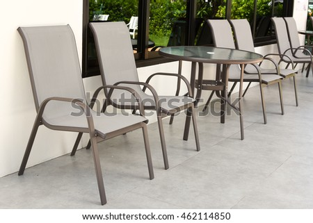 Garden table and chairs with water resistant outdoor. Chair with vintage color effect. garden chairs and table. Patio furniture in a beautiful garden.
