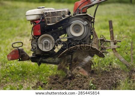garden tiller working in the field, motion blur - stock photo