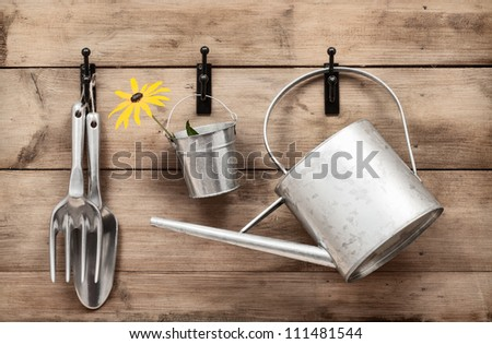 Garden tools hanging and watering can on shed door with vintage feel - stock photo