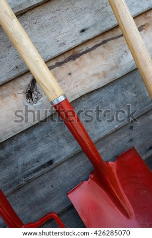 Garden tools hoe and garden fork on siding background. - stock photo