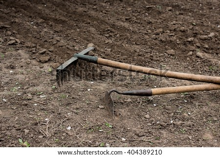 garden tools. rake and hoe on the ground - stock photo