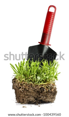 Garden turf with grass and trowel isolated on white.
