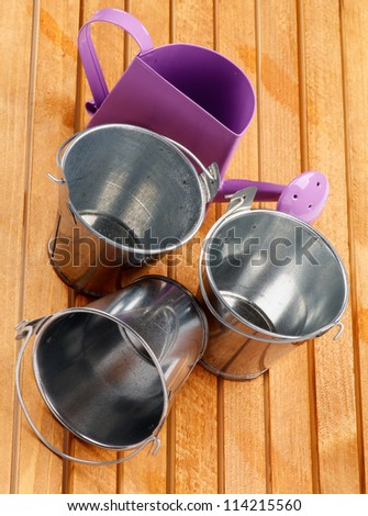 Garden Utensil with Tin Buckets and Watering Can on wooden background - stock photo
