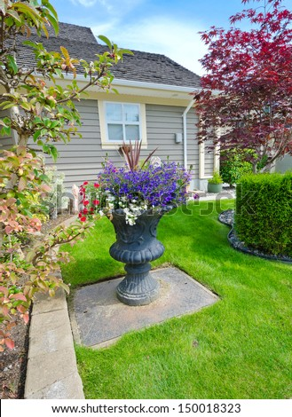 Garden Vase With Nicely Decorated Colorful Flowers And Trimmed Front Yard  Lawn. Landscape Design.