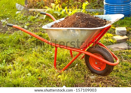 Garden wheelbarrow full of humus soil