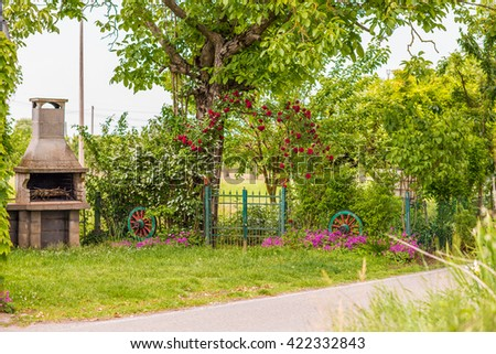 garden with concrete oven, arched gate and flowers