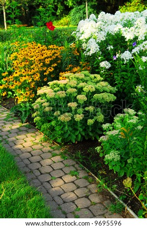 Garden with paved path and blooming flowers in late summer - stock photo