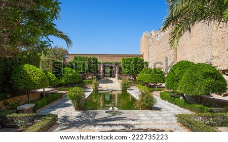 Garden with pond and fountains in the Alcazaba of Almeria. On the right the wall of the fortress.