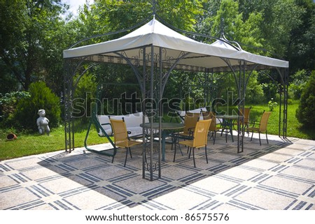 Garden with tent and garden furniture - stock photo