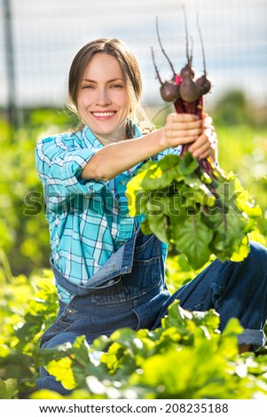 Garden work. Young woman with organic vegetables, bunch of beetroots in the garden. focus on face - stock photo