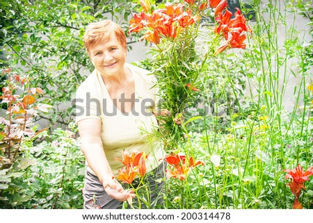 Gardener active senior elderly woman with bouquet (bunch) of freshly plucked flowers (lilies). Caucasian positive smiling woman has healthy lifestyle. Female model in sunny summer day in the garden.  - stock photo