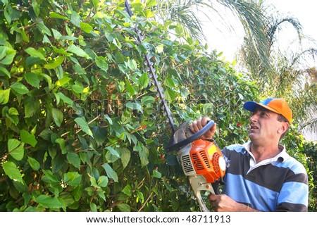 Gardener by work with saw. - stock photo