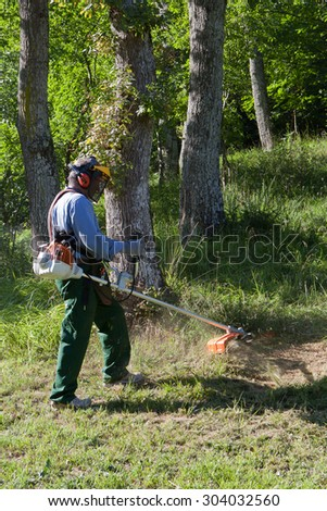 Gardener cutting grass with string trimmer - stock photo