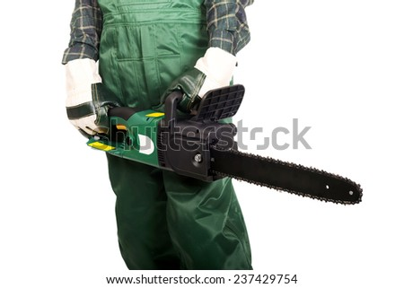 Gardener in green uniform and gloves holding chainsaw. - stock photo