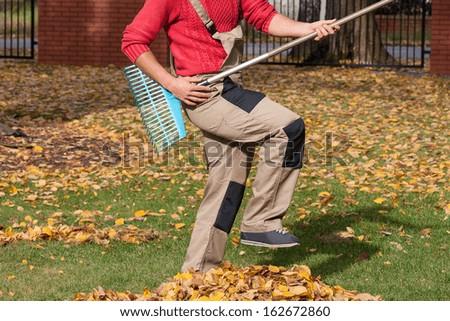 Gardener pretending that his playing guitar during raking leaves - stock photo