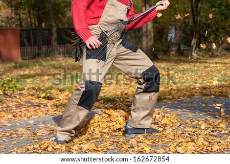 Gardener pretending that the rake is a guitar - stock photo
