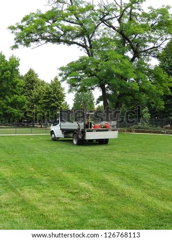 Gardener's truck and equipment on freshly cut grass