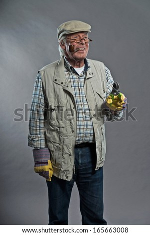 Gardener senior man with hat holding pruning shears. Wearing glasses and smoking pipe. Studio shot against grey. - stock photo