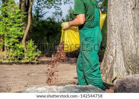 Gardener spills garden bark  to protect plants - stock photo