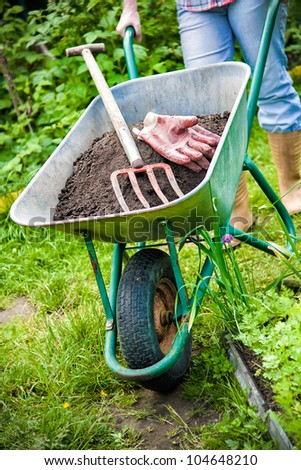 gardener with a wheelbarrow full of humus in the garden - stock photo