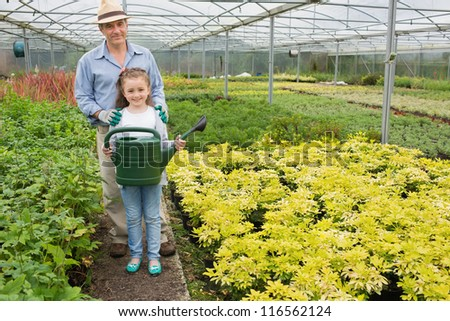 Gardener with granddaughter holding watering can in greenhouse