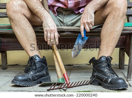 gardener with hairy legs in boots resting on a bench - stock photo