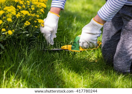 Gardener working on green lawn, cutting grass - stock photo