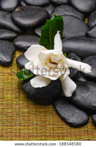 gardenia flowers and black stones on mat