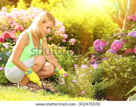 Gardening. Blonde young woman planting flowers in garden