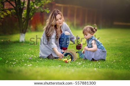 Gardening discovering, family and teaching concept. Happy mother with little daughter are planting flowers into the ground. Spring