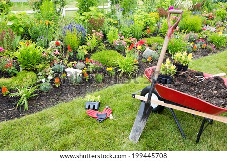 Gardening equipment ready for use in a garden with beautiful plants and flowers - stock photo
