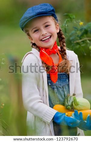 Gardening, gardener, kid - lovely girl with picked vegetables - stock photo