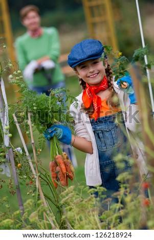 Gardening, gardener, kid - lovely girl working in vegetable garden - stock photo