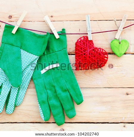 Gardening Hand Gloves. The beautyful feeling of gardening. Some hearts and gardening hand gloves on a wooden background. Square Format. For more see my portofolio