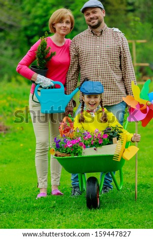Gardening - happy family with wheelbarrow working in the garden