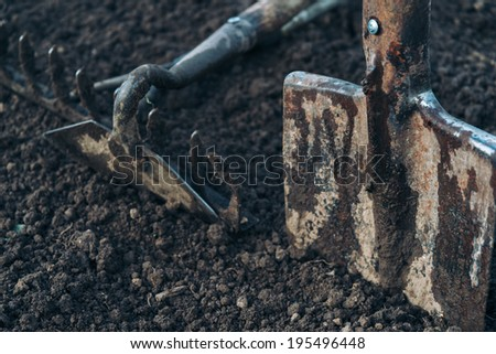 Gardening hoe and shovel on land - stock photo
