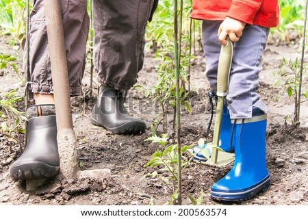 Gardening. Legs of woman and child (boy) is on the soil with gardening tools. Female and male model in the rubber boots involved in horticulture. Woman and kid has healthy lifestyle. Close up.   - stock photo