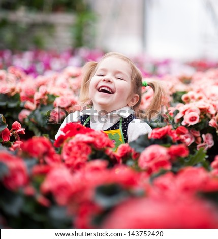 Gardening - little girl with seedlings in the greenhouse - stock photo