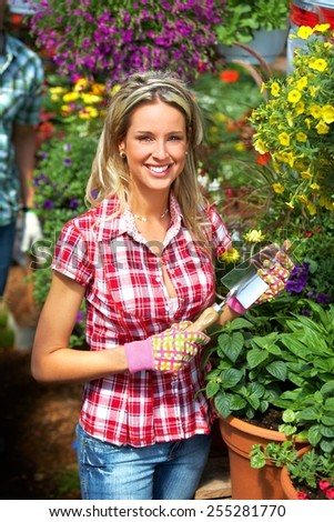 Gardening people. Woman working in greenhouse with flowers.