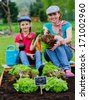 Gardening, planting, cultivation - young girl with mother working in vegetable garden - stock photo