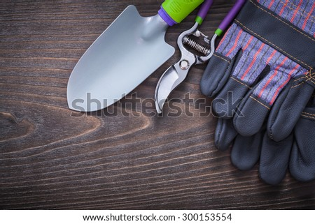 Gardening protective gloves hand spade and secateurs on vintage wooden board agriculture concept. - stock photo