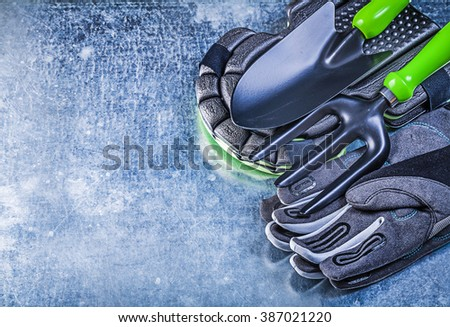 Gardening protective gloves knee protectors hand shovel trowel fork on metallic background agriculture concept.