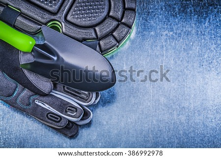 Gardening protective gloves knee protectors hand spade on metallic background agriculture concept. - stock photo