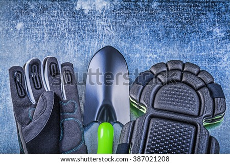 Gardening safety gloves knee pads hand shovel on metallic background agriculture concept. - stock photo
